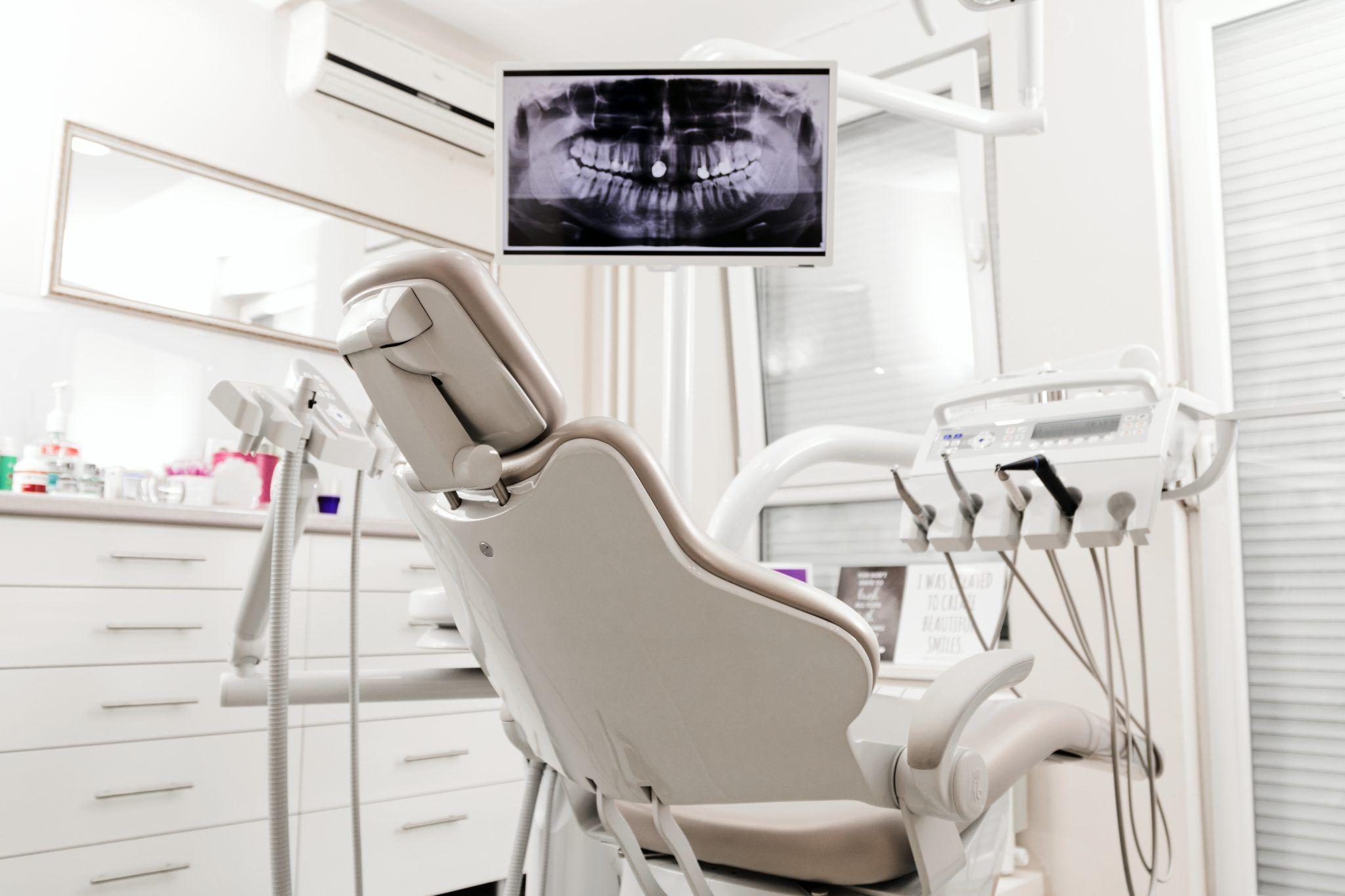 Consultório dentista, cadeira, instrumentos e radiografia no monitor